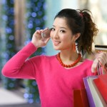 Young woman holding up her mobile phone and credit card out shopping