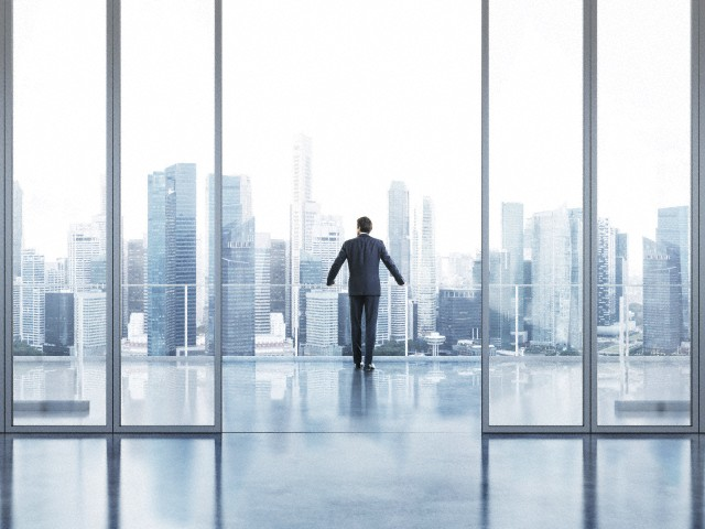 Businessman standing on a balcony and looking at city skyline
